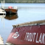 Words Trout Lake painted on row boat that is on shore with lake in background.